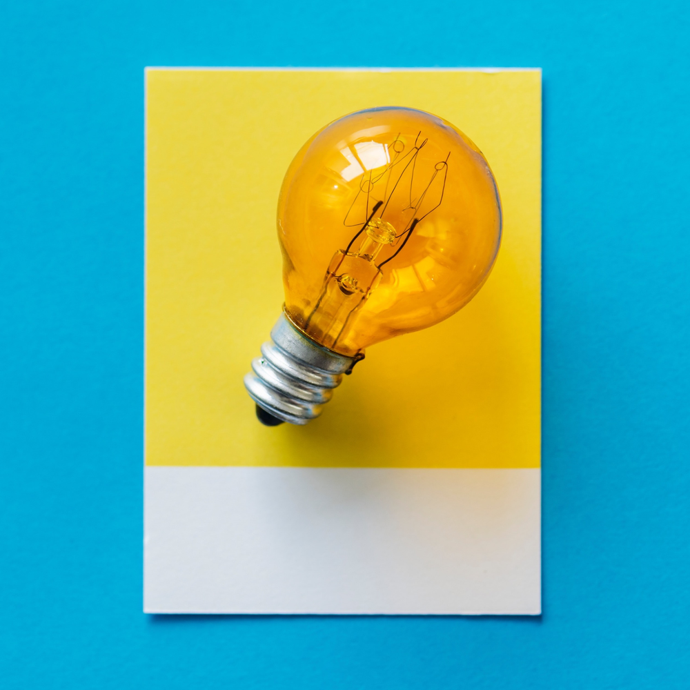 A light bulb on a yellow background piece of paper
