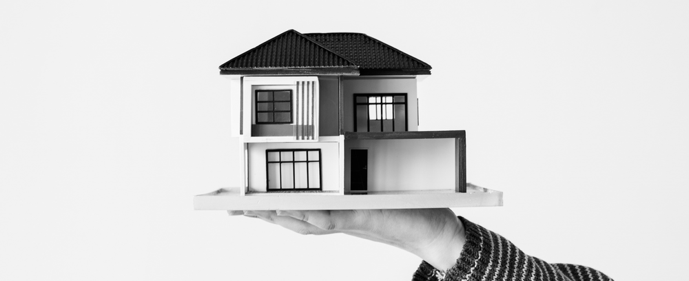 A person holding a miniature diagram of a house